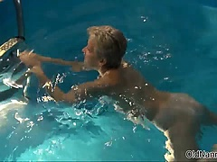 Sexy nanny plays with a toy in the pool and