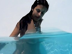 Naughty girl stripping in the swimmingpool