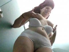 Voyeur spying on a busty mature brunette changing clothes